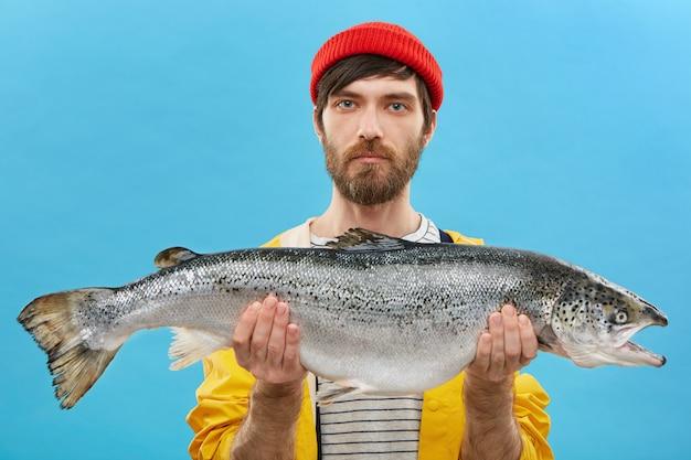 Horizontales porträt des erfolgreichen anglers mit bart, der riesigen fisch hält, den er fing. junger fischer gekleidet lässig stehend mit riesigen forelle. mann mit frischem fang. angeln und erholung Kostenlose Fotos