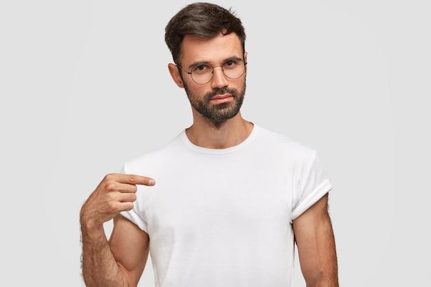 Horizontales porträt des gutaussehenden unrasierten mannes mit stoppeln, gekleidet in lässigem weißem t-shirt, zeigt auf leeren kopienraum für ihr design, trägt eine brille. ernster mann verkäufer von kleidung Kostenlose Fotos