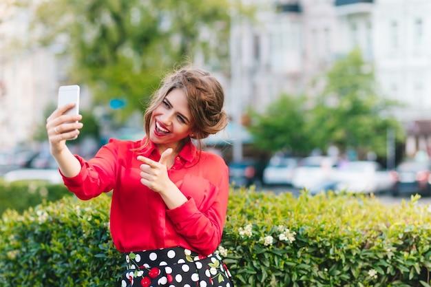 Horizontales porträt des hübschen mädchens, das im park steht. sie trägt eine rote bluse und eine schöne frisur. sie macht ein selfie-porträt am telefon. Kostenlose Fotos