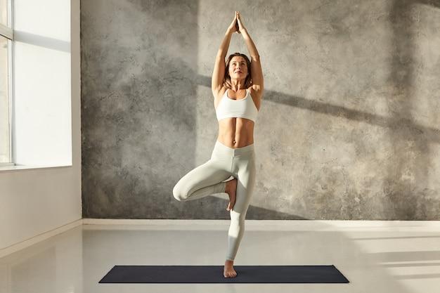 Horizontales porträt in voller länge einer attraktiven jungen frau mit einem schönen athletischen körper, der yoga praktiziert und einen stilvollen sport-bh und leggings trägt, wobei er eine vrikshasana- oder baum-yoga-pose in einem großen fitnessstudio macht Kostenlose Fotos