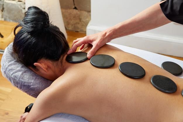 Hot stone massage in frau zurück physiotherapeut Premium Fotos