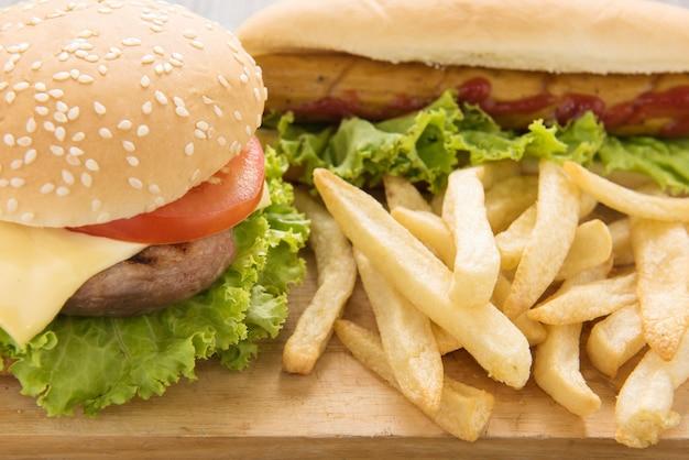Hotdogs, hamburger und pommes-frites auf dem holztisch. Premium Fotos
