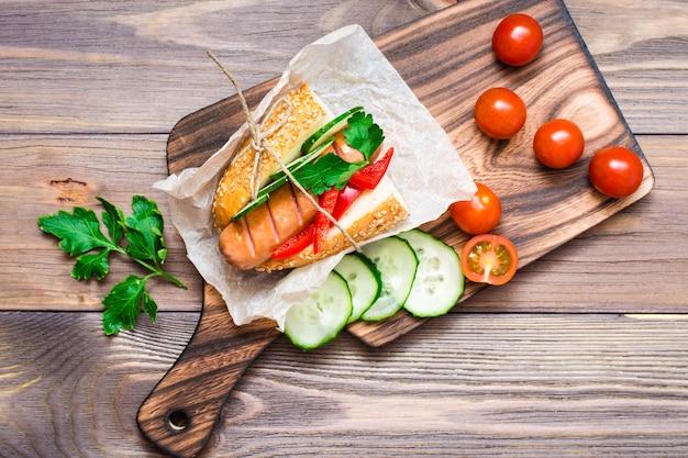 Hotdogs mit brötchen des indischen sesams und frischgemüse auf einer platte auf einem holztisch Premium Fotos