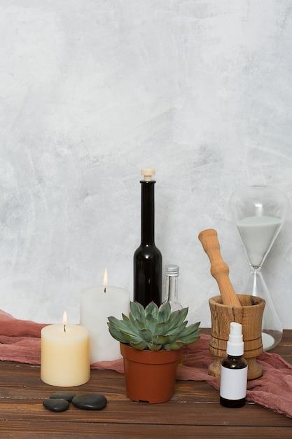 Hour glas; kaktuspflanze; brennende kerze; letzter; ätherisches öl; hölzerner mörtel und pastell auf tisch gegen wand Kostenlose Fotos