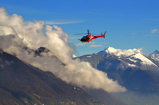 Hubschrauber fliegt zwischen den wolken über den schneebedeckten bergen Kostenlose Fotos