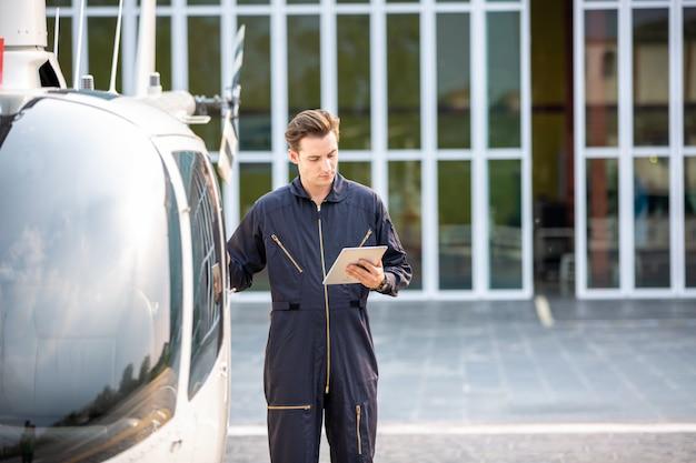 Hubschraubertechniker, der gegen hubschrauber im flughafen steht Premium Fotos