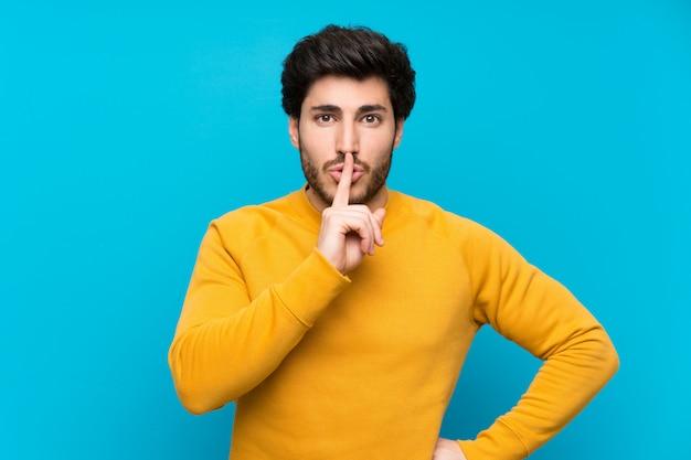 Hübsch über der lokalisierten blauen wand, die ein zeichen der ruhegeste einsetzt finger in mund zeigt Premium Fotos