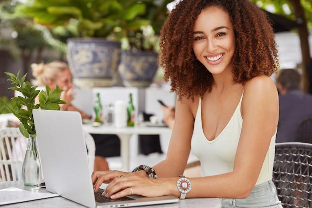 Hübsche afroamerikanische weibliche modell-tastaturen etwas auf laptop-computer, verbunden mit kostenlosem drahtlosem internet im café, schreibt neuen artikel für ihren blog Kostenlose Fotos