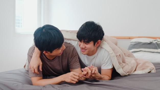 Hübsche asiatische homosexuelle paare, die zu hause auf bett sprechen. der junge asiatische glückliche lgbtq + kerl entspannen sich, verbringen zusammen romantische zeit, nachdem er morgens im schlafzimmer am modernen haus aufgewacht ist. Kostenlose Fotos