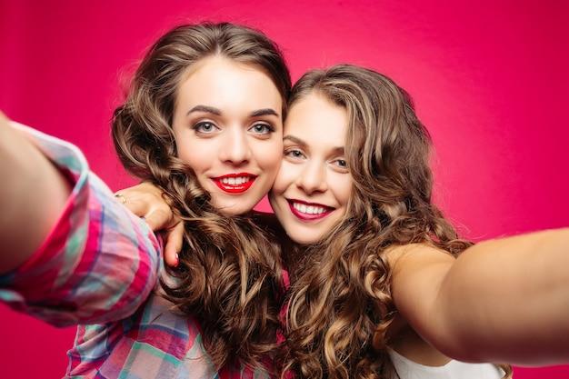 Hübsche beste freunde, die selfie mit kamera nehmen. Premium Fotos