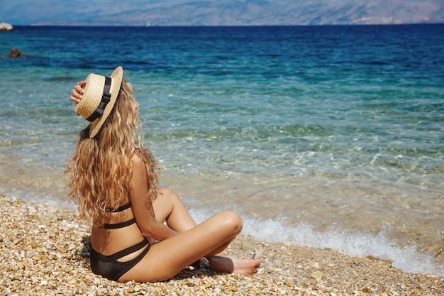 Hübsche blonde frau im schwarzen bikini und im strohhut am strand Premium Fotos