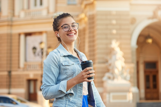 Hübsche blonde junge frau in gläsern geht in einer jeansjacke durch die stadt, trinkt kaffee, hört in kopfhörern lieblingsmusik Kostenlose Fotos