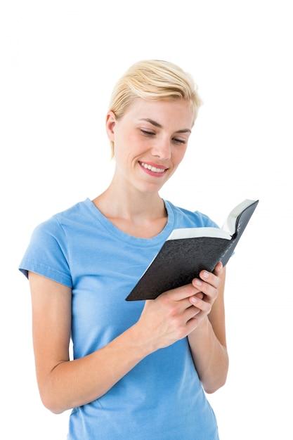 Hübsche blondine, die bibel liest Premium Fotos