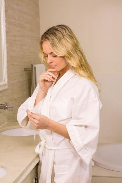 Hübsche blondine, die einen schwangerschaftstest im badezimmer halten Premium Fotos