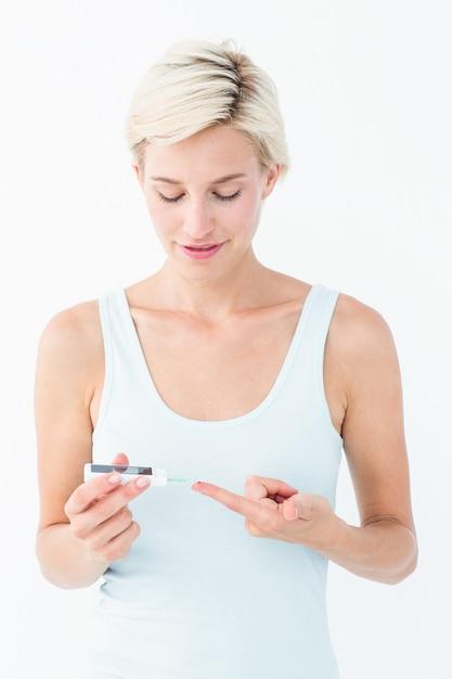Hübsche blondine, die ihren blutzuckerspiegel prüft Premium Fotos
