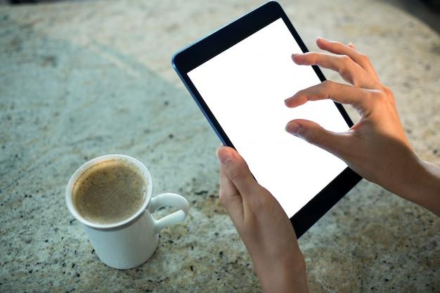 Hübsche blondine, die tablet-computer verwenden Premium Fotos
