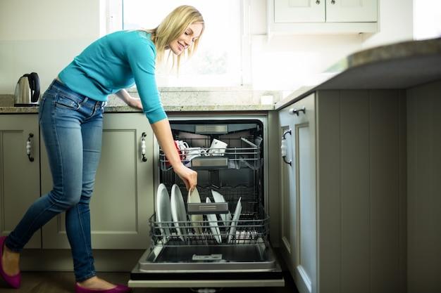 Hübsche blondine, welche die spülmaschine leeren Premium Fotos