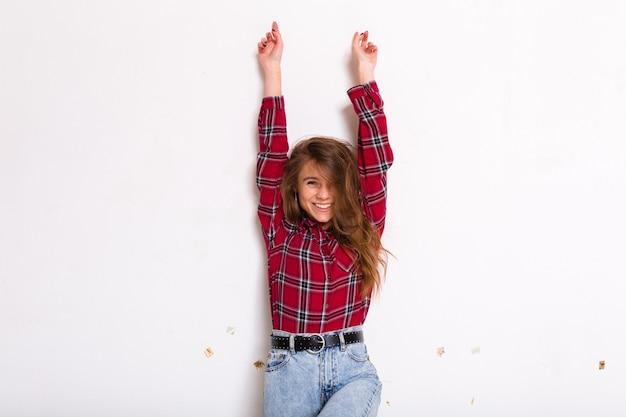Hübsche charmante junge frau mit dem langen haar, das mit den händen oben aufwirft und lächelt, das rotes hemd auf weiß trägt Kostenlose Fotos