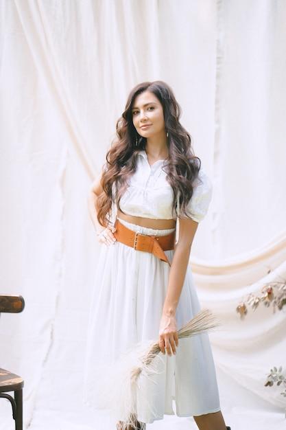 Hübsche dame im langen weißen kleid mit gürtel, der dekoration hält und im garten mit weißer wand während des tages schaut. Kostenlose Fotos