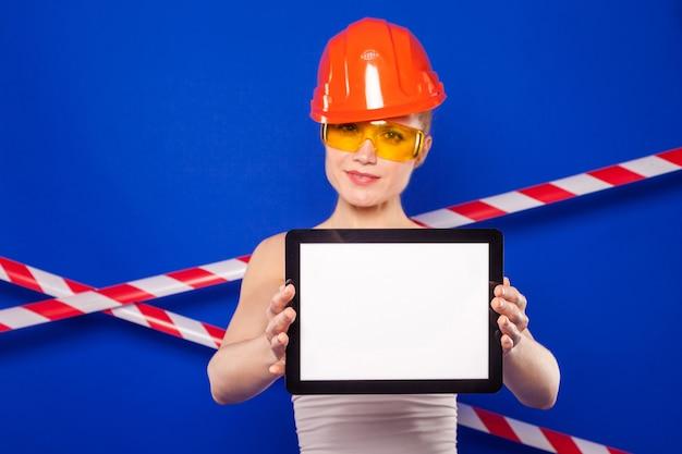 Hübsche erbauerfrau im weißen hemd, im erbauergürtel, im sturzhelm, in den erbauergläsern, in den jeansshorts und in den snickern halten leere tablette Premium Fotos
