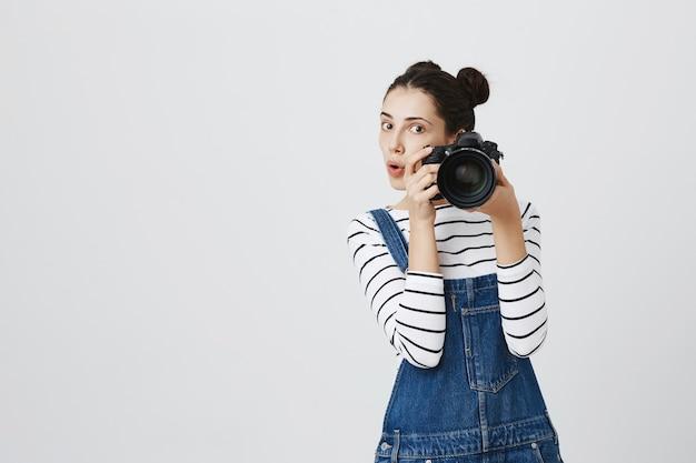 Hübsche fotografin, die fotos macht und jemanden fotografiert Kostenlose Fotos