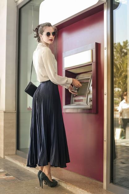 Hübsche frau an einem geldautomaten Premium Fotos