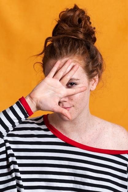 Hübsche frau der nahaufnahme mit gestreiftem blusen- und haarbrötchen Kostenlose Fotos