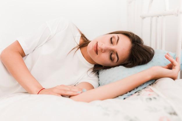 Hübsche frau, die auf bett schläft Kostenlose Fotos