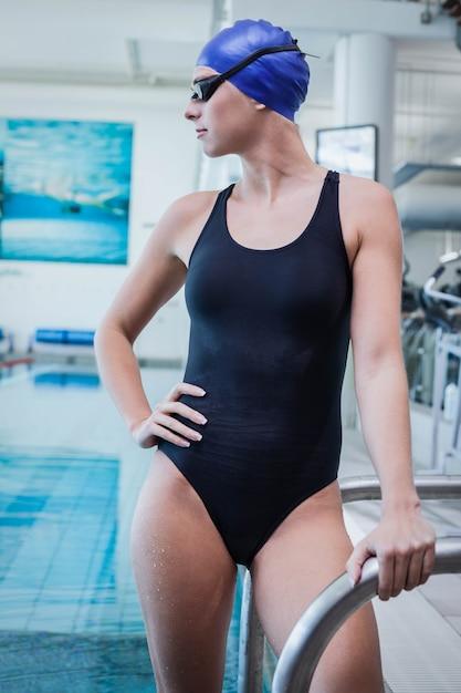 Hübsche frau, die auf der poolleiter am swimmingpool steht Premium Fotos