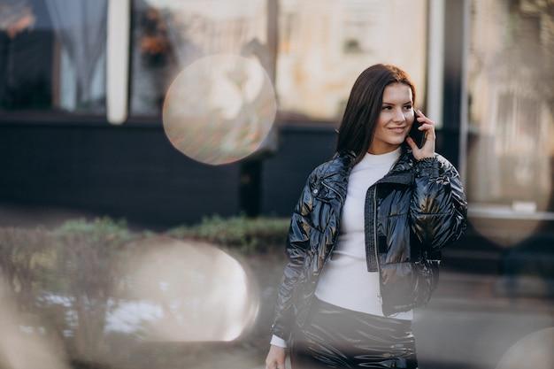 Hübsche frau, die draußen telefon im park verwendet Kostenlose Fotos