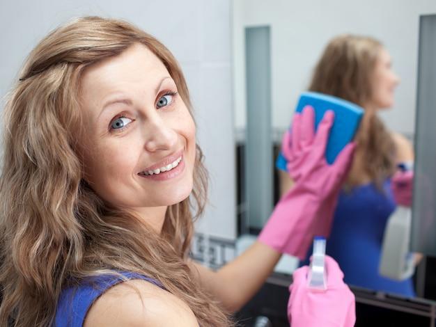 Hübsche frau, die einen badezimmerspiegel säubert Premium Fotos
