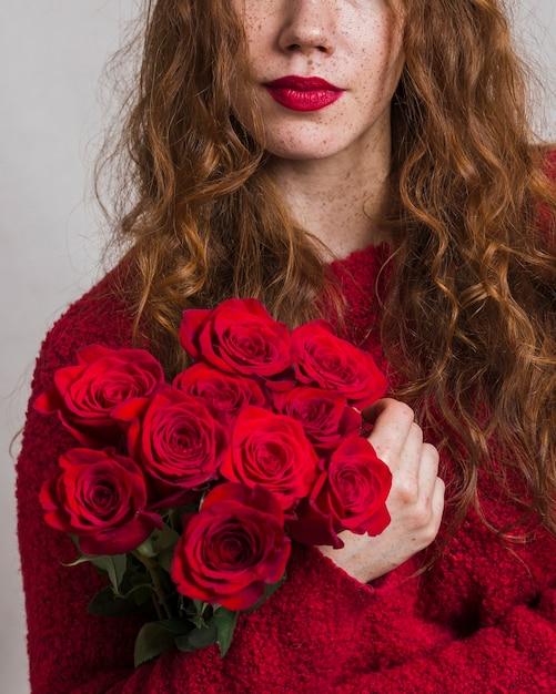 Hübsche frau, die einen blumenstrauß von rosen hält Kostenlose Fotos
