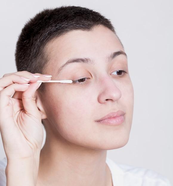 Hübsche frau, die einen wattestäbchen verwendet, um ihr make-up zu säubern Kostenlose Fotos