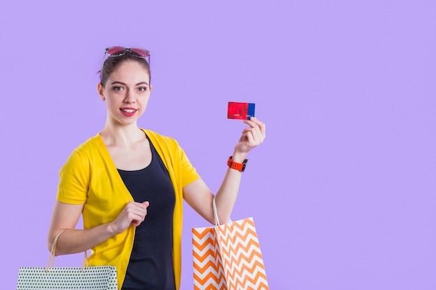 Hübsche frau, die geschenkkarte mit dem halten der einkaufstasche vor purpurroter wand zeigt Kostenlose Fotos