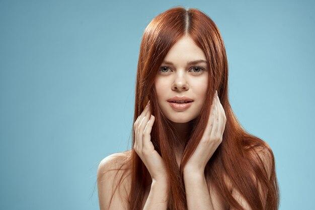Hübsche frau, die haare in den händen hält, die nackten schultern des beschnittenen blauen hintergrunds der ansicht pflegen. Premium Fotos