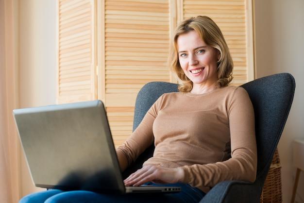 Hübsche frau, die laptop sitzt und verwendet Kostenlose Fotos