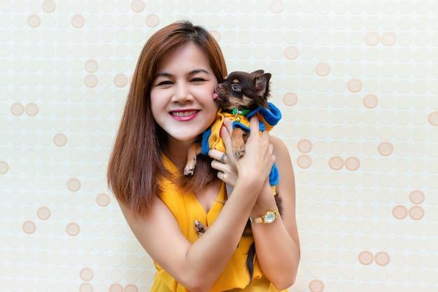 Hübsche frau, die mit einem kleinen hund spielt Kostenlose Fotos