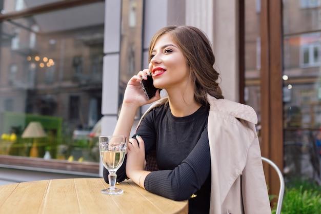 Hübsche frau gekleidet in schwarzem kleid und beigem graben mit stilvoller frisur und roten lippen auf einer terrasse, die am telefon spricht Kostenlose Fotos