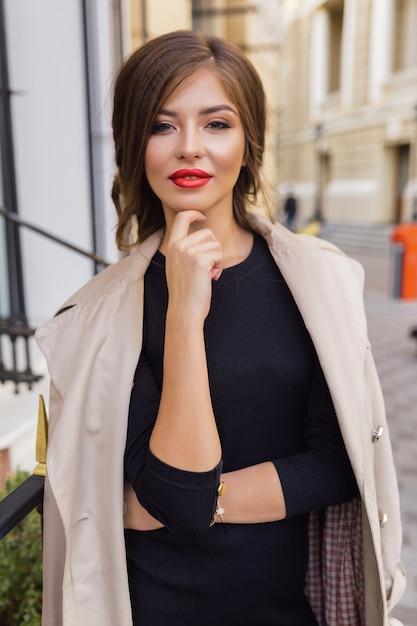 Hübsche frau gekleidet in schwarzem kleid und beigem trenchcoat mit stilvoller frisur und roten lippen auf der straße Kostenlose Fotos