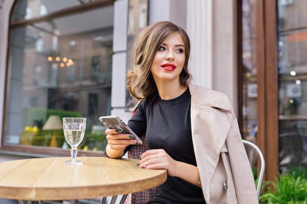 Hübsche frau gekleidet in schwarzem kleid und beigem trenchcoat mit stilvoller frisur und roten lippen auf einer terrasse Kostenlose Fotos