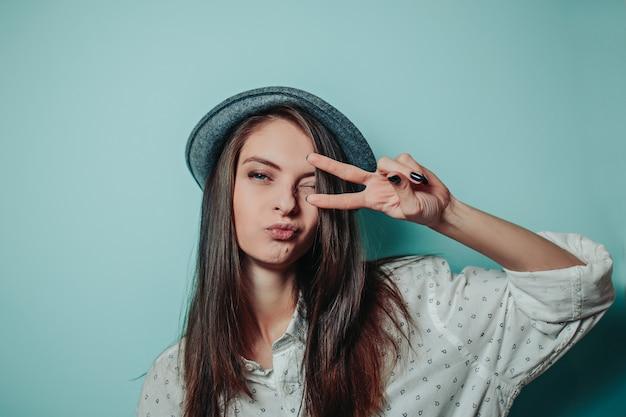 Hübsche frau in einem grauen hut mit langen haaren und weißem hemd. frau zeigt friedenszeichen mit den fingern. Premium Fotos
