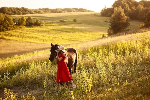 Hübsche frau in einem heuhut und in einem roten kleid steht mit einem pferd auf dem grünen feld Kostenlose Fotos