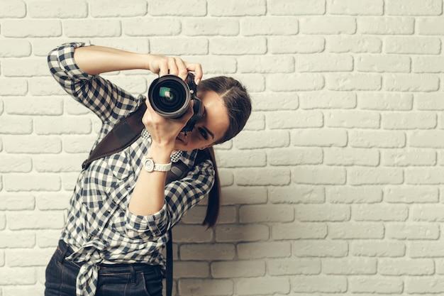 Hübsche frau ist ein professioneller fotograf mit dslr-kamera Premium Fotos