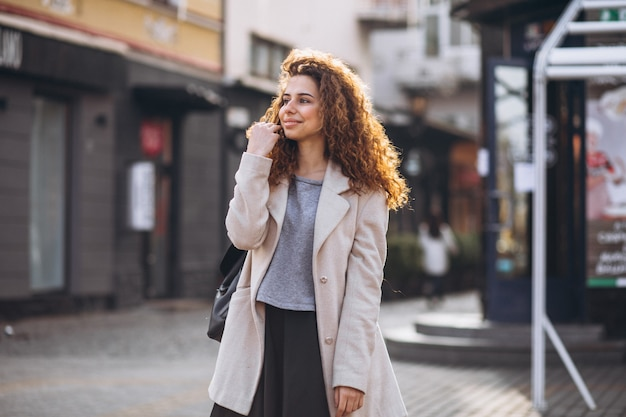 Hübsche frau mit dem gelockten haar gehend an einer caféstraße Kostenlose Fotos
