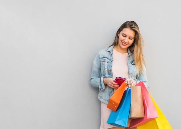 Hübsche frau mit einkaufstüten mit smartphone Kostenlose Fotos
