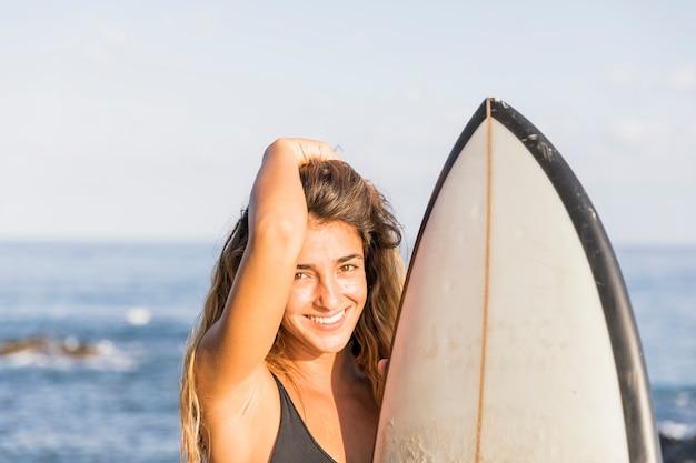 Hübsche frau mit rührendem haar des surfbrettes Kostenlose Fotos