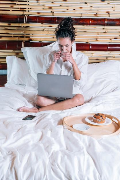Hübsche frau mit telefon und laptop im bett Premium Fotos