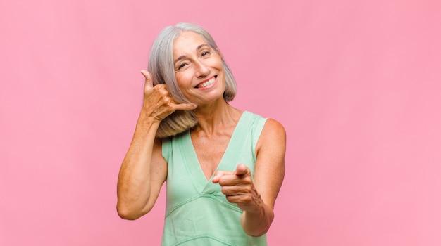 Hübsche frau mittleren alters, die glücklich und fröhlich lächelt, hand winkt, sie begrüßt und begrüßt oder sich verabschiedet Premium Fotos