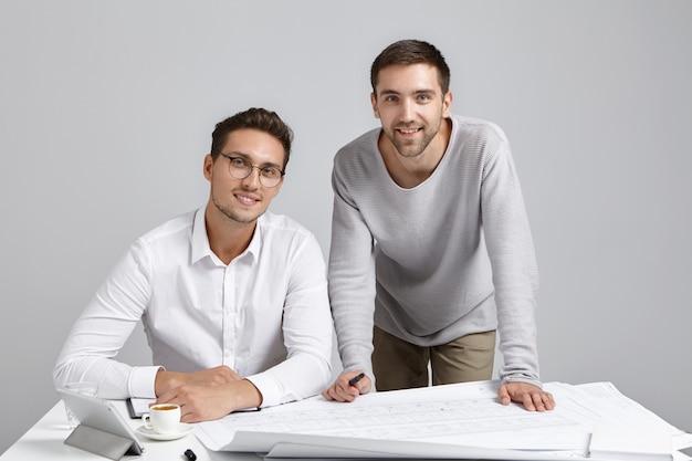 Hübsche, fröhliche junge männliche unternehmer oder designarbeiter sitzen am arbeitsplatz, umgeben von blaupausen Kostenlose Fotos