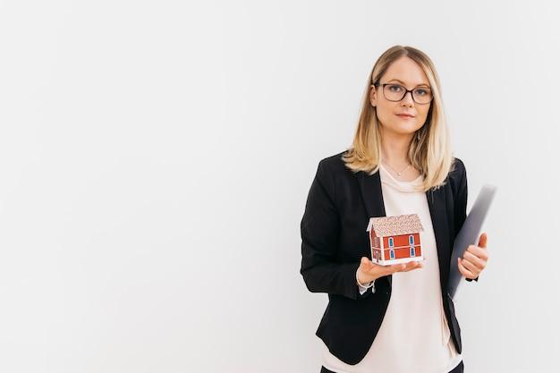 Hübsche geschäftsfrau, die hausmodell und -dokument lokalisiert auf weißem hintergrund hält Kostenlose Fotos